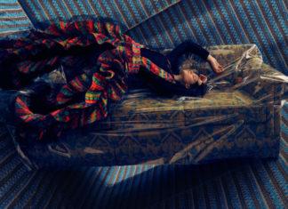 Na zdjeciu widzimy podloge oraz sciany oblozone niebieskim materialem we wzory na srodku stoi wzorzysta kanapa w przezroczystej folii nienaturalnie wygieta modelka ubrana we wzorzyste kolorowe ubranie opiera sie o nia