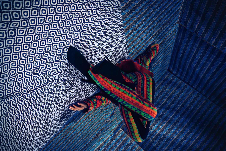 Na zdjeciu widzimy modelke wygieta w nienaturalnej pozie za tlo robia poprzyklejane do sciany niebieskie wzorzyste tkaniny