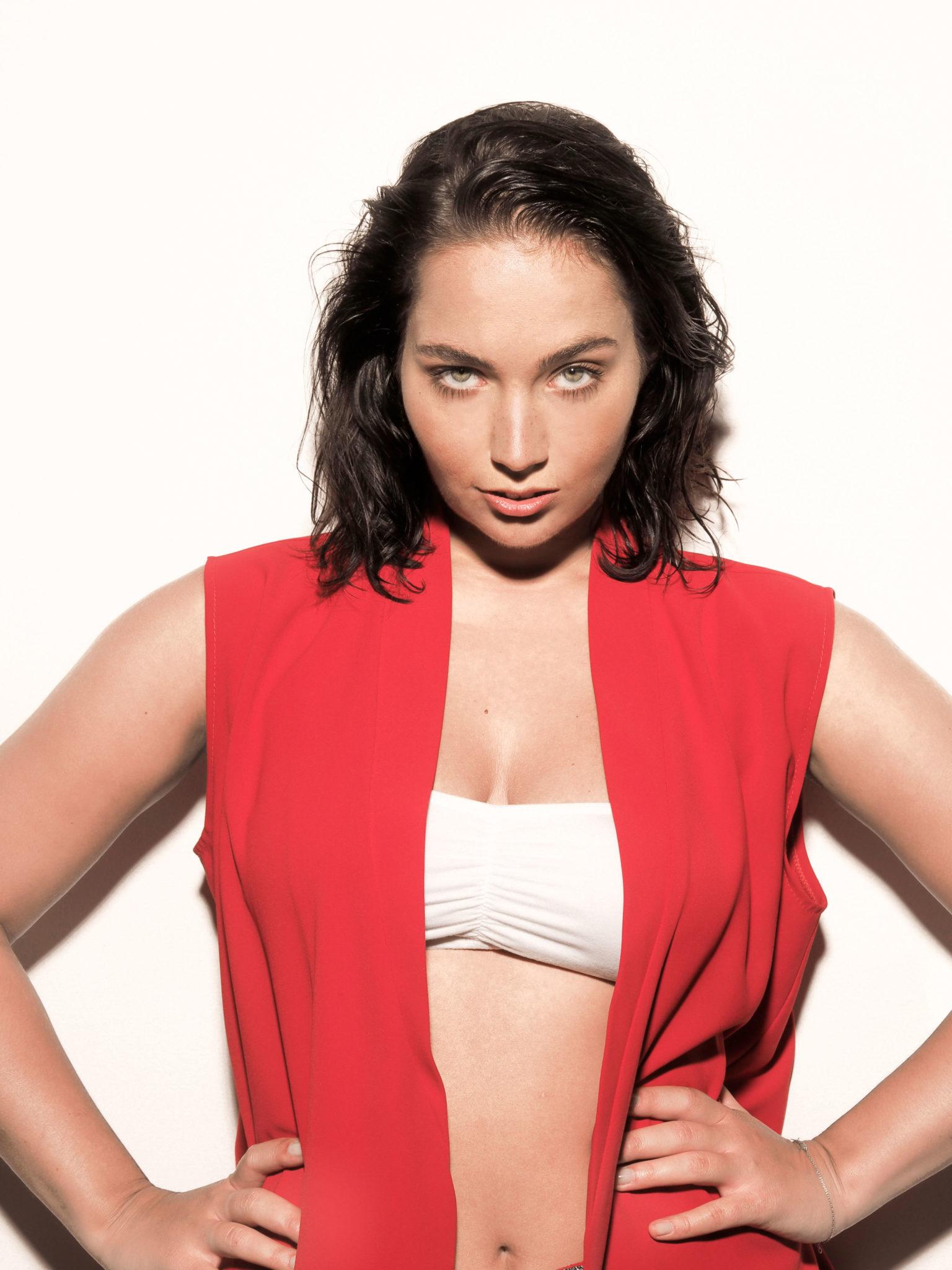 Na bialym tle stoi brunetka ubrana w bialy top i czerwona kamizelke podparta rekami pod boki