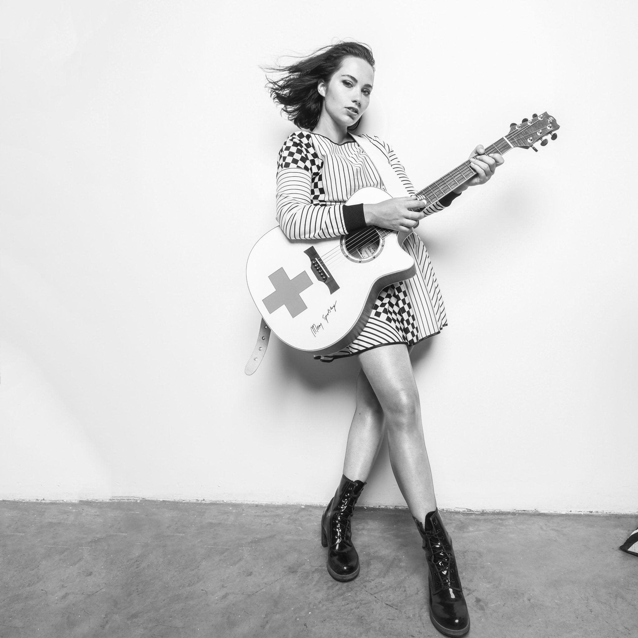 Czarno biale zdjecie na ktorym widac kobiete w krotkich ciemnych wlosach ubrana w sukienke w i czanre buty na tle bialej sciany z gitara w reku