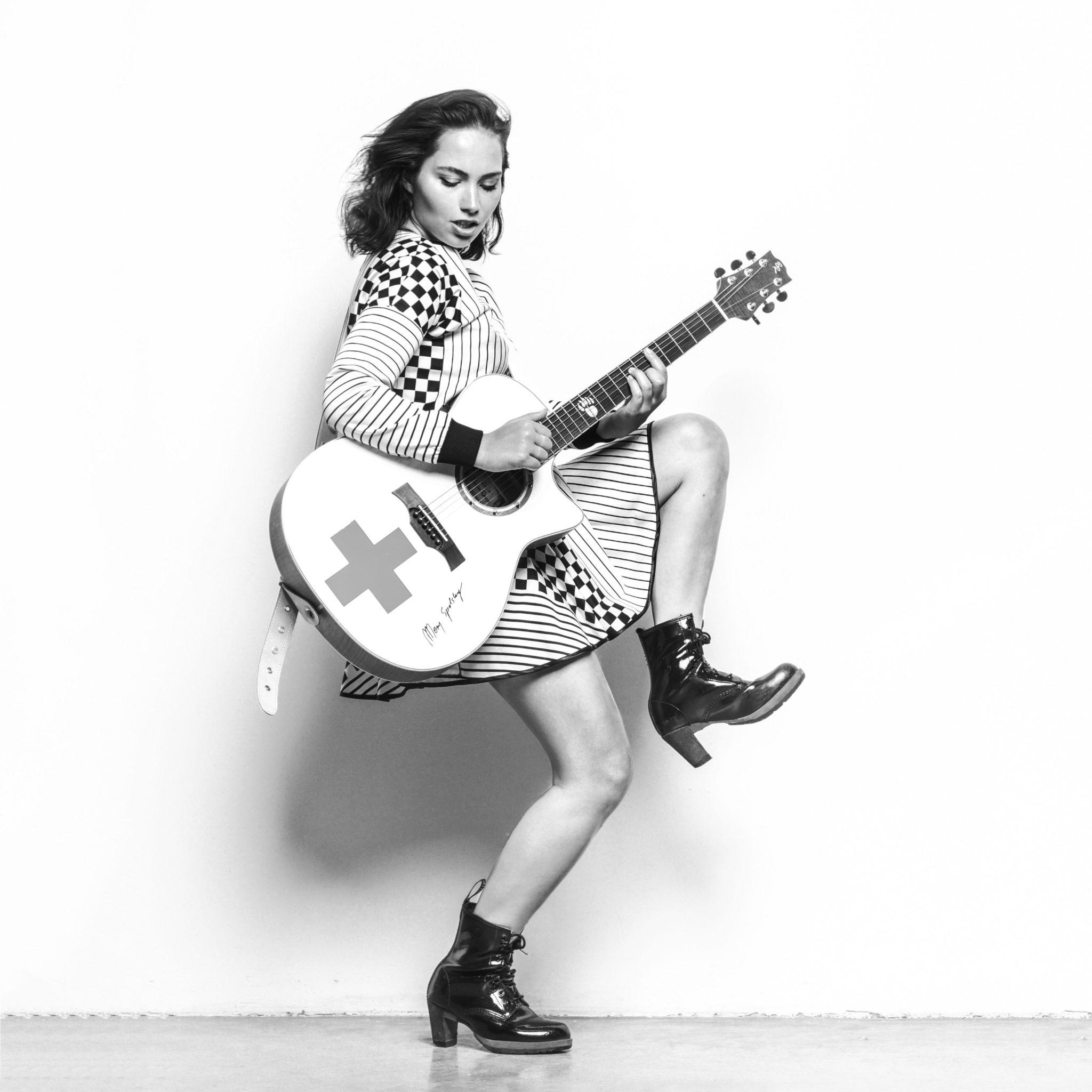 Na czarno bialym zdjeciu widac mloda kobiete w sukience w paski prawa noge ma uniesiona a w rekach trzyma gitare