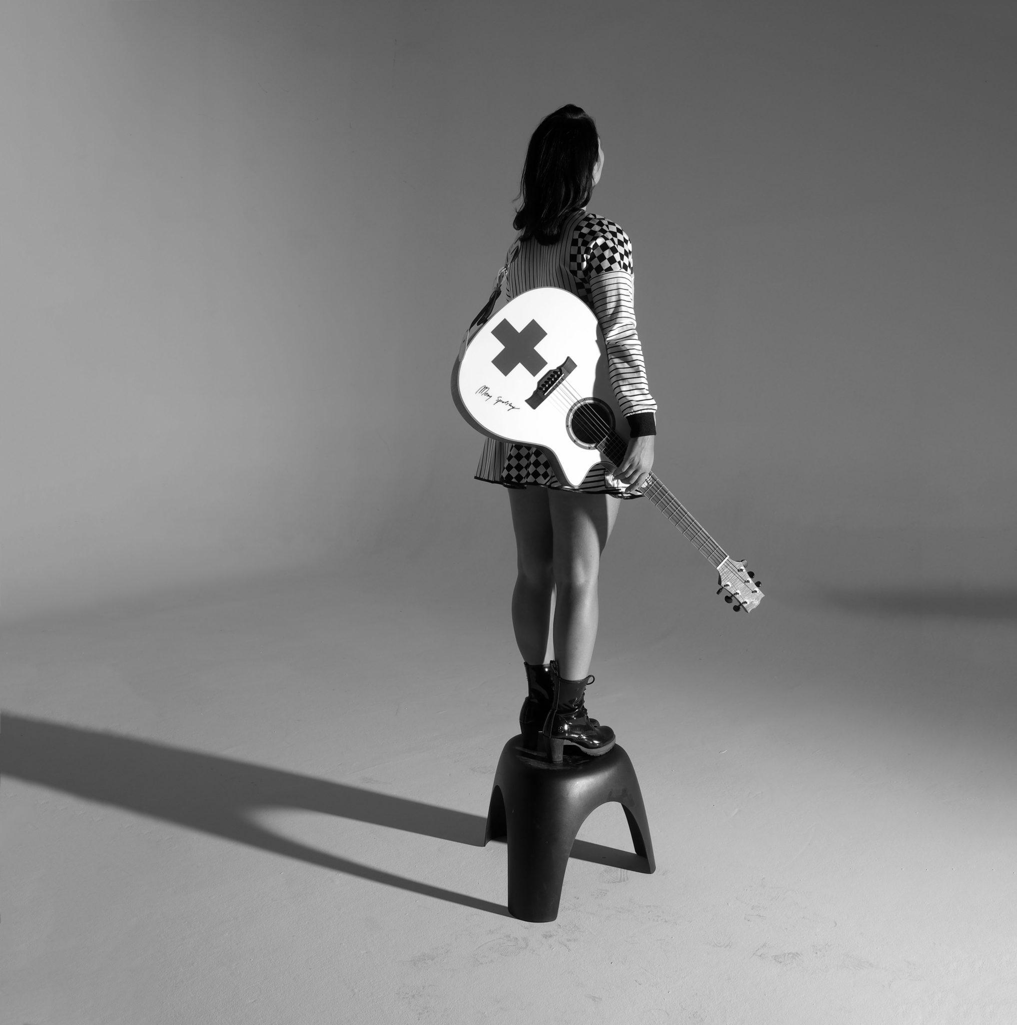 Na czarno bialym zdjeciu widzimy mloda kobiete odwrocona plecami trzymajaca w reku gitare