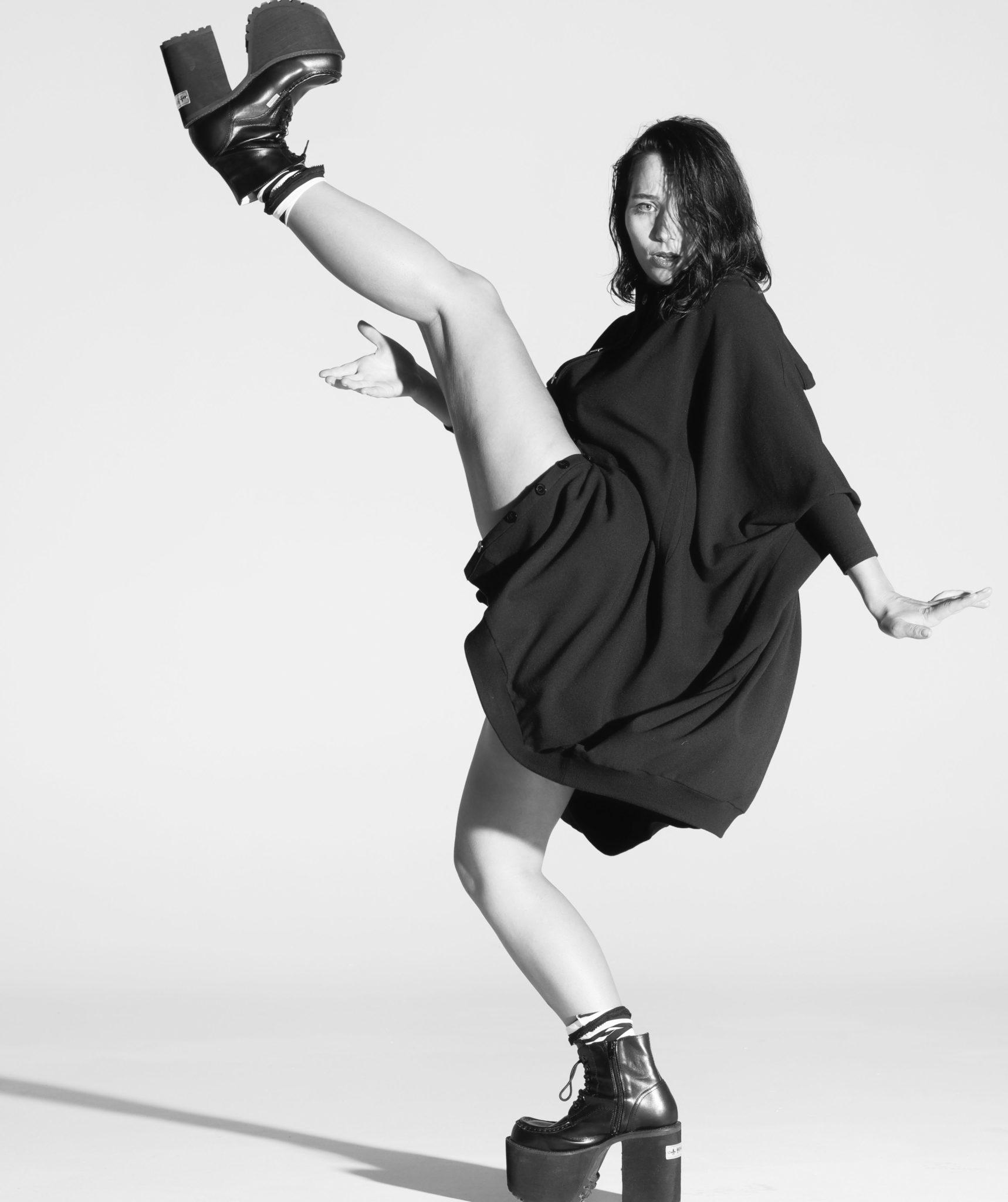 Na czarno bialym zdjeciu widzimy kobiete ubrana w czarna workowata spodnice i buty na duzym kutornie i obcasie ciemne wlosy i uniesiona w lewo noga