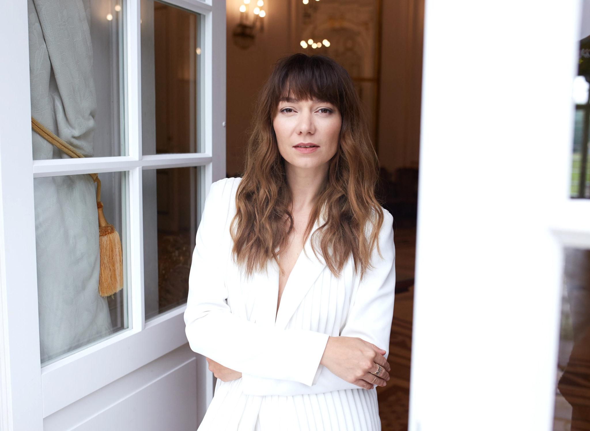 Brunetka ubrana w biala marynarke stoi w bialych drzwiach delikatnie oparta o framuge trzym sie za lokcie