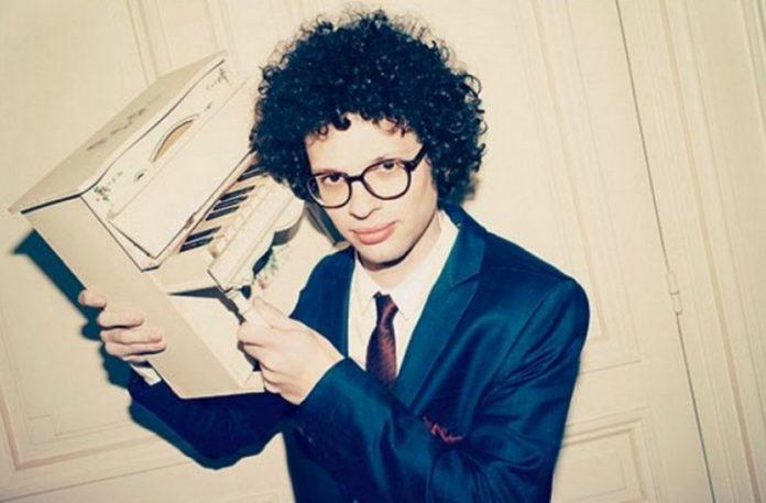 Chłopak z kręconymi włosami, trzymający w ręku małe pianino