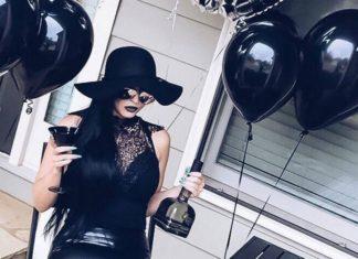 Kobieta ubrana na czarno, dookoła czarne balony