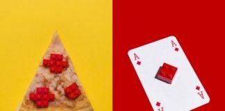 Kawałek pizzy z klockami lego zamiast pepperoni i karta asa z klockiem lego na środku