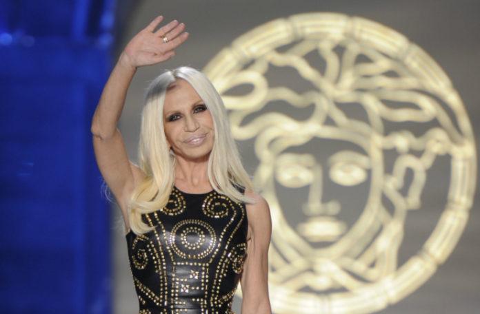 Kobieta machająca ręką na tle logo Versace