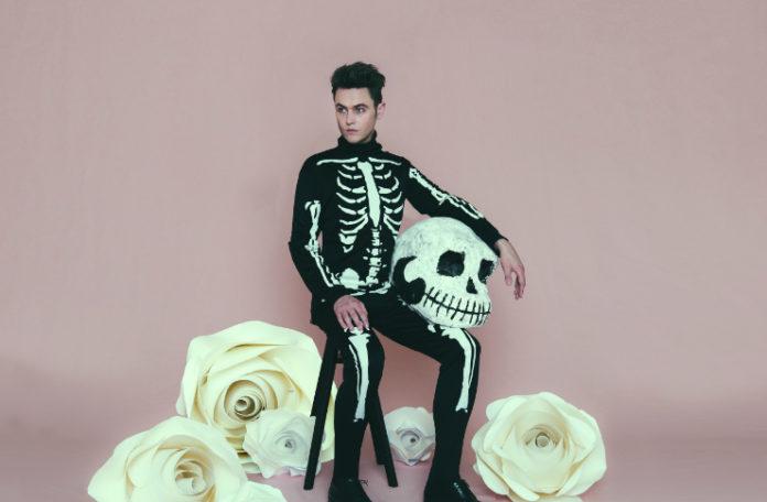 Mężczyzna w kostiumie szkieletu na różowym tle