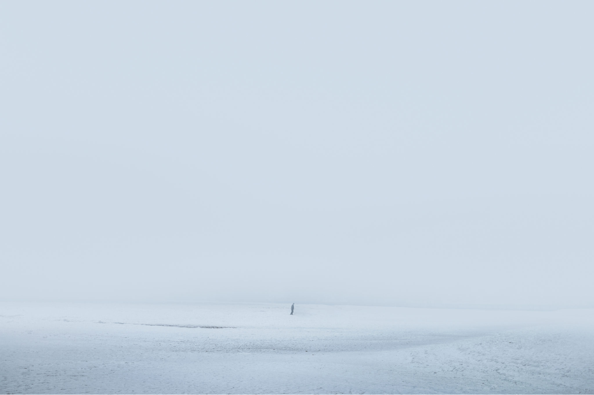 Na zdjeciu widzimy biala od sniegu zamglana plaze w oddali widac zarys postaci czlowieka