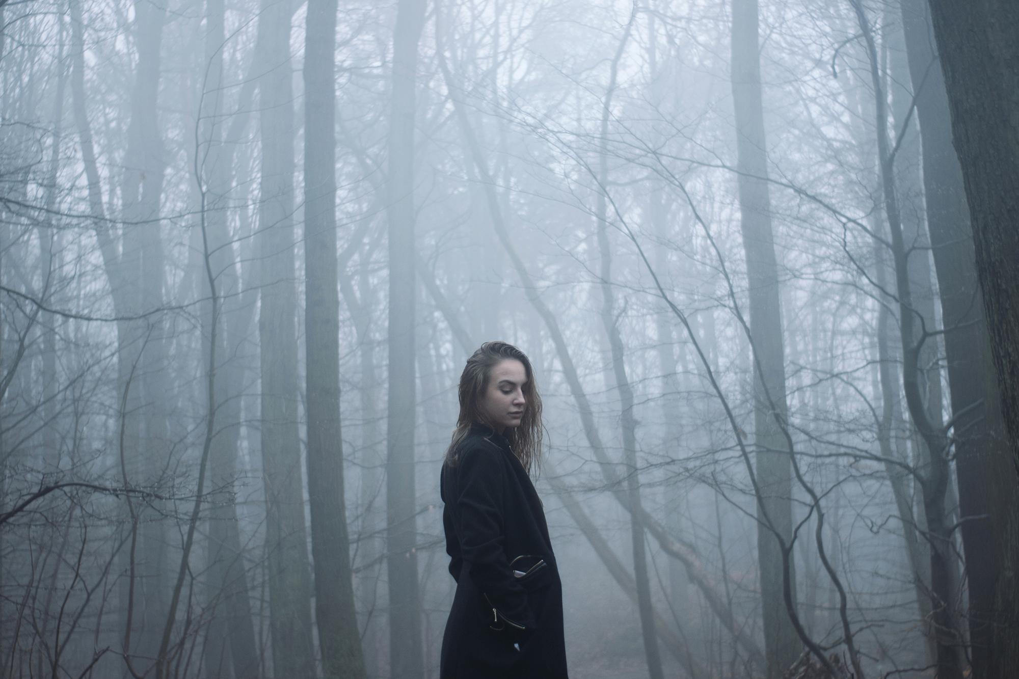 Na zdjeciu widac las pokryty mgla a pomiedzy drzewami stoi profilem kobieta w czarnym plaszczem