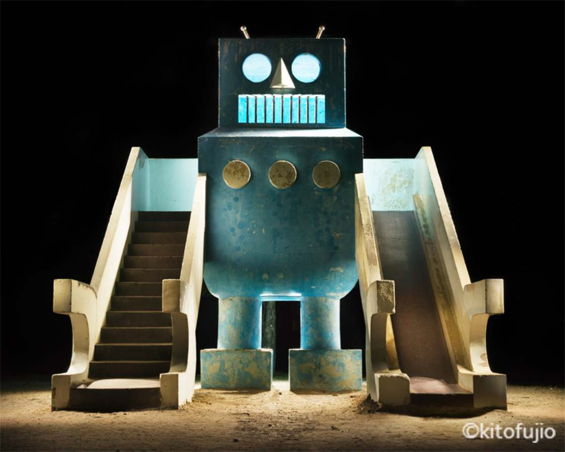 Duży betonowy element placu zabaw w formie niebieskiego oldschoolowego robota.