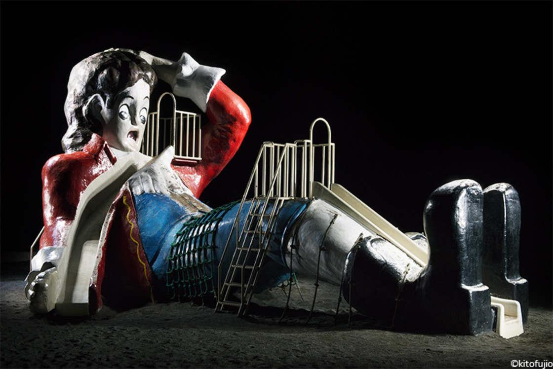 Duży betonowa zjeżdżalnia w formie leżącej postaci męskiej z ciemnymi włosami, czerwoną marynarką, czarnymi długimi butami.
