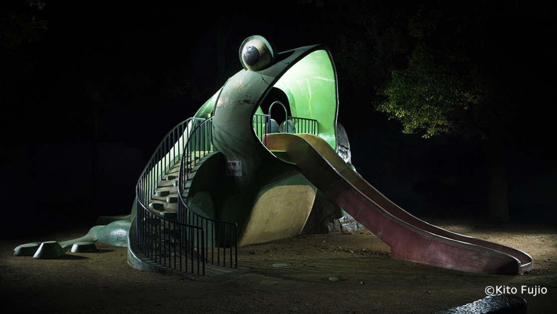 Duża betonowa zjeżdżalnia w formie zielonej żaby z wyciągniętym językiem.