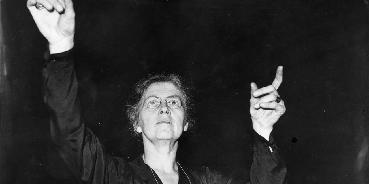 Czarno białe zdjęcie przedstawiające starszą kobietę w okularach z krótkimi włosami, z rękami uniesionymi przed siebie.