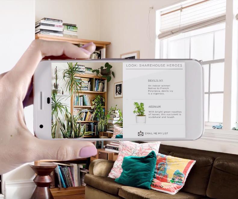 Dłoń kobiety, trzymająca telefon komórkowy. Wykonuje nim zdjęcie salonu, na które nałożone zostały rośliny zielone. W tle widok salonu bez roślin.