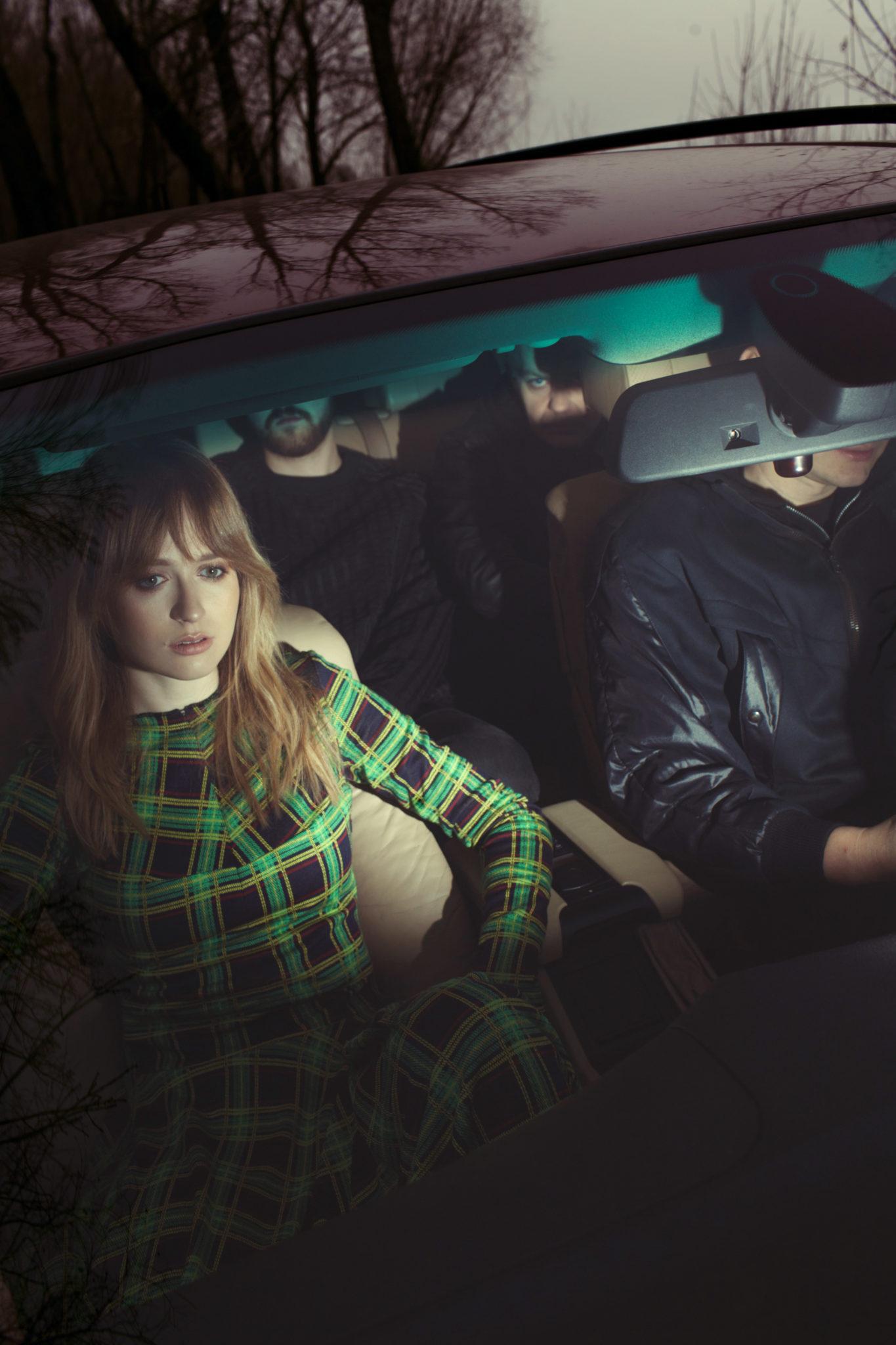 Na zdjeciu widzimy oswietlone wnetrze samochodu ktory prowadzi mezczyzna ubrany w czarna kurtke skorzana obok niego siedzi blondynka w zielonej sukience a na tylnym siedzeniu mezczyzni