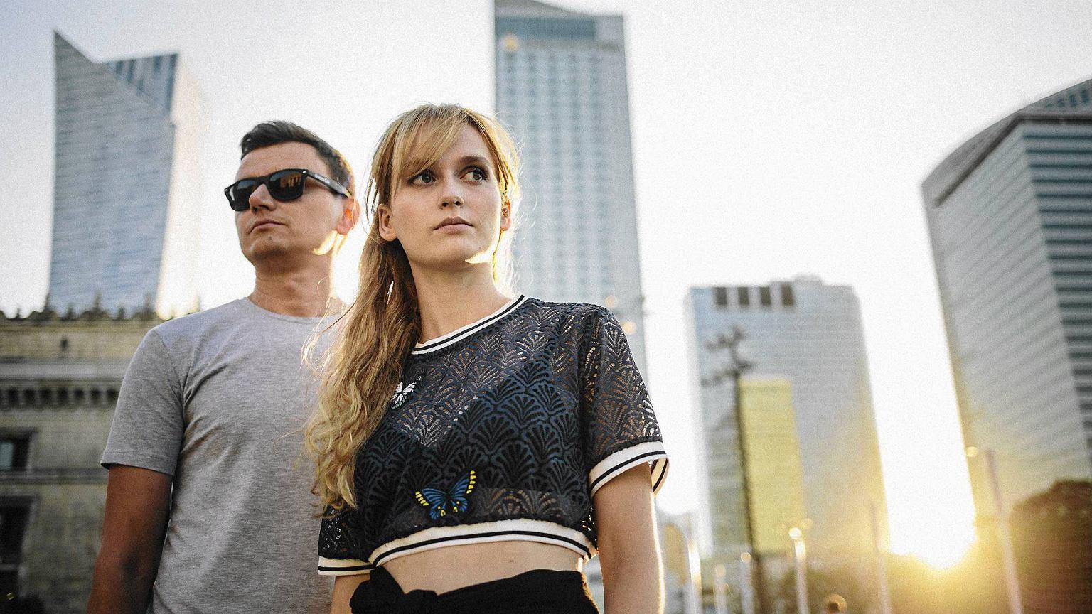 Na zdjeciu widzimy mezyczyzne w okularach przeciwslonecznych oraz kobiete blondynke na tle architektury warszawskiej