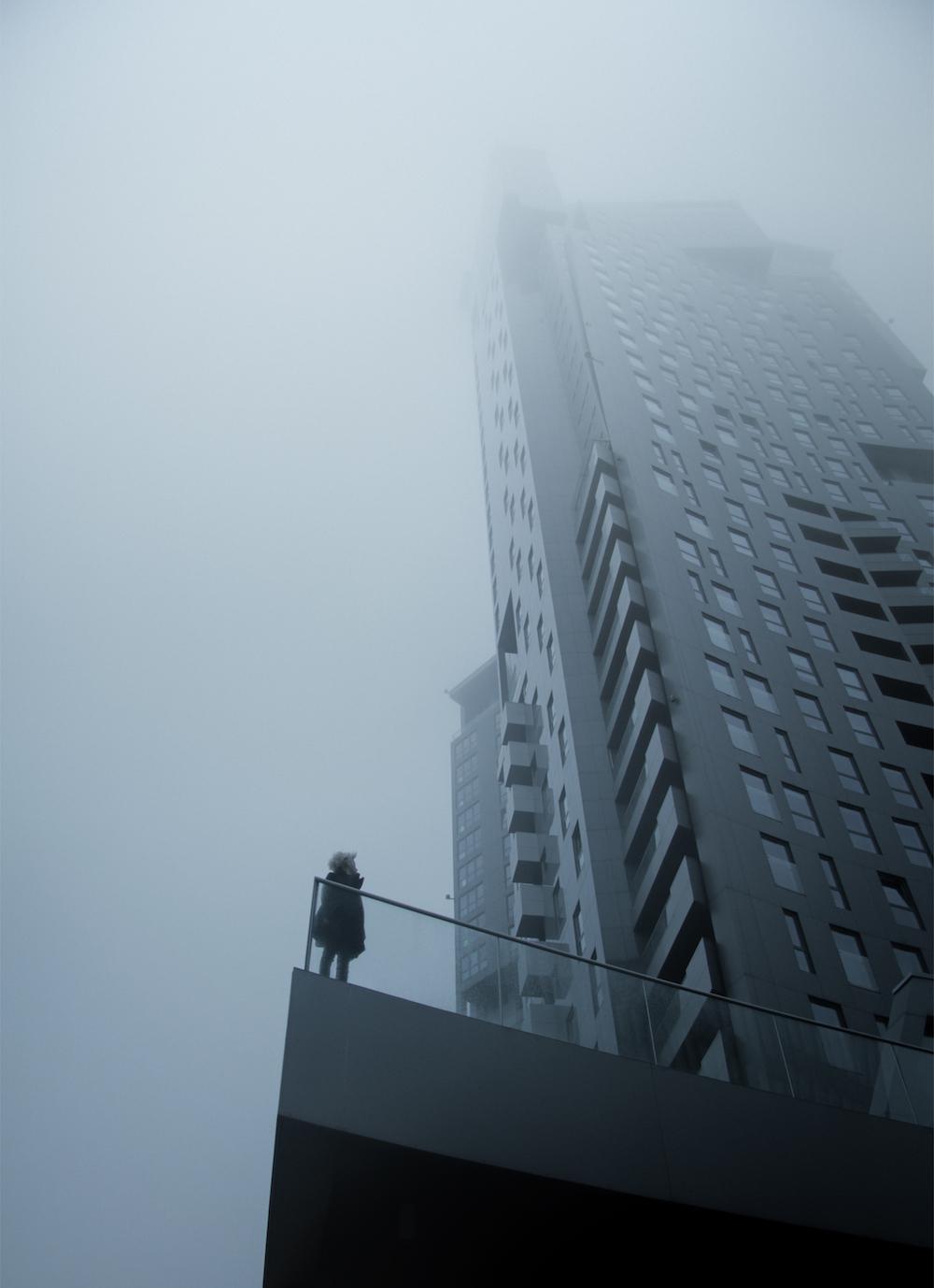 Na zdjeciu widzimy drapacz chmur we mgle na balkonie szarego budynku stoi drobna postac kobiety