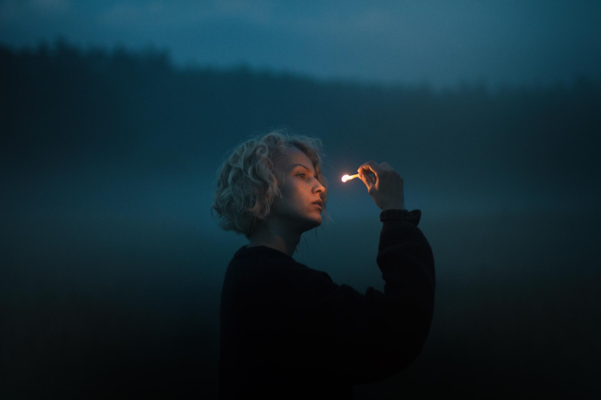 Na zdjeciu widzimy laske z lasem w tle wszystko jest bardzo zamglone na pierwszym planie bokiem stoi mloda dziewczyna ubrana na czarno blondynka w reku trzyma zapalona zapalke, na ktora patrzy