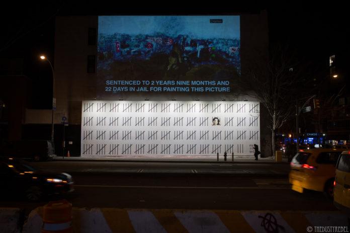 """Ulica po zmroku, na ścianie wielki mural, na białym tle seria czarnych kresek przypominających kraty więzienne, za jedną wizerunek kobiety, w prawym dolnym rogu napis """"Free Zehra Dogan"""". Nad muralem projekcja obrazu i napis."""