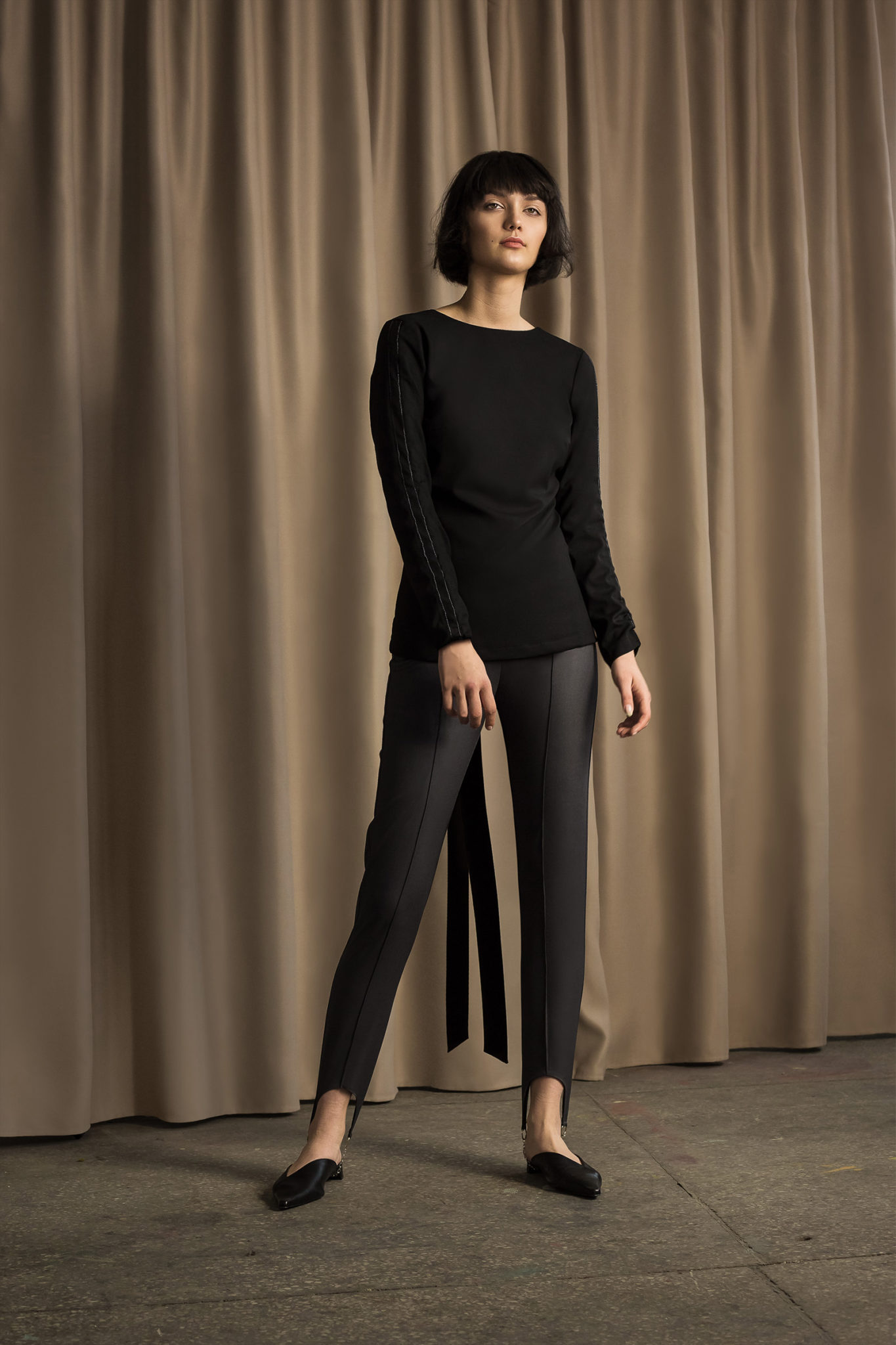Na zdjeciu widzimy kobiete ubrana na czarno w spodnie i bluzke w krotkich wlosach pozuje na brazowym tle zrobionym z materialu