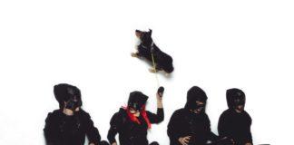 Czwórka ludzi ubrana na czarno na białym tle i pies na smyczy