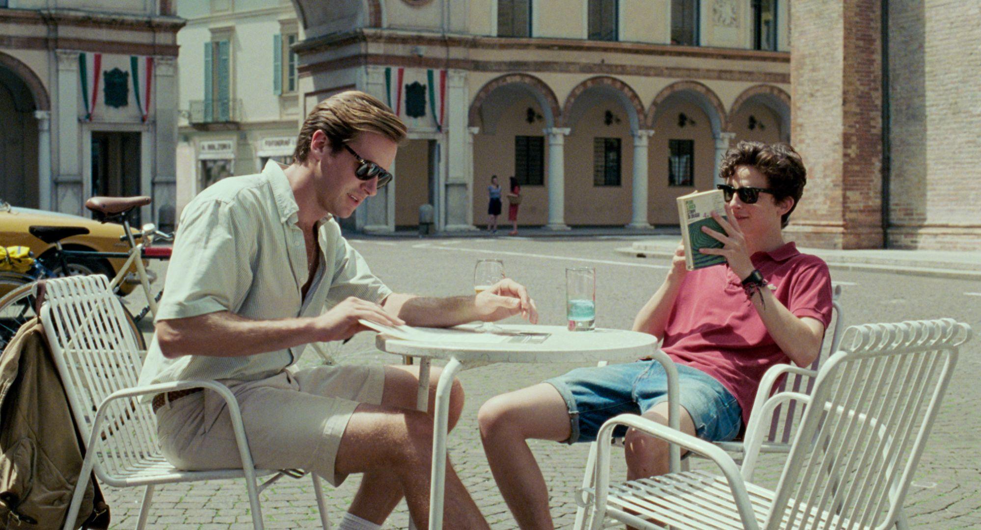 Mężczyzna i nastoletni chłopiec siedzą przy stoliku w miasteczku i czytają książki