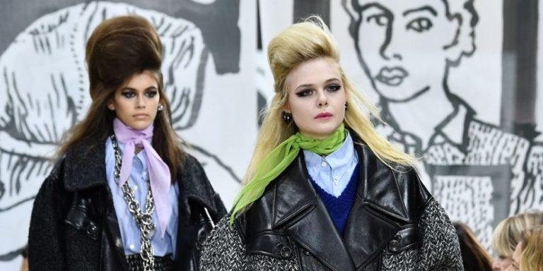 dwie kobiety jedna blondynka druga brunetka obie noszące wysokie, tapirowane fryzury z mocnym ciemnym makijażem idące po wybiegu w ciemnych kurtkach
