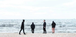 Czterech mężczyzn stojących nad brzegiem morza