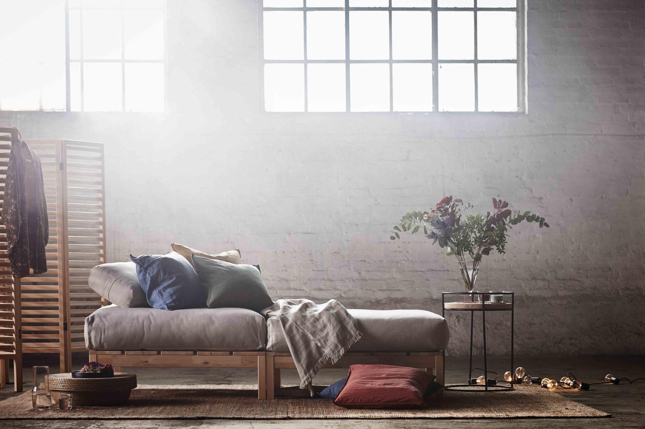 Duże jasne pomieszczenie z szarą sofą z poduszkami, stolikiem nocnym, drewanianym parawanem.