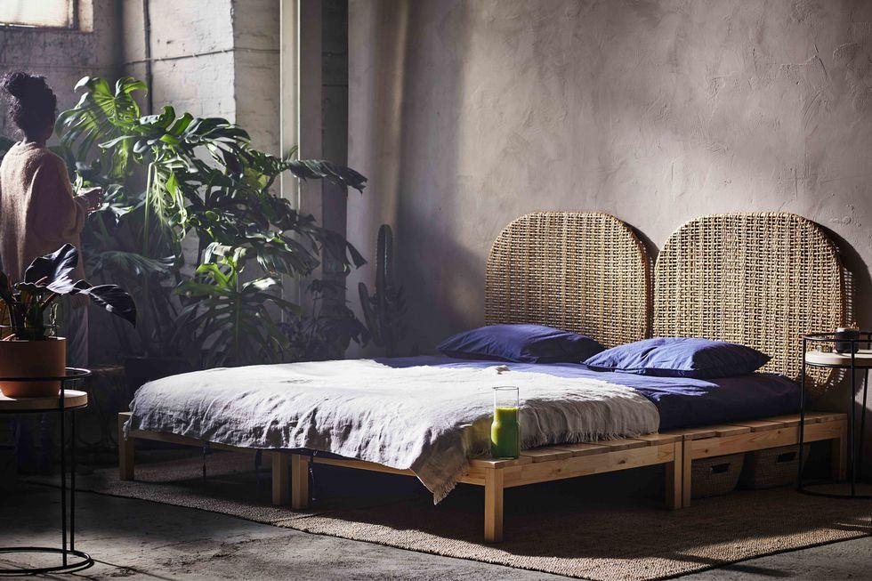 Dwuosobowe drewniane łózko z ratanowym zagłówkiem w dużym, jasnym pomieszczeniu, obok ciemnoskóra kobieta i duże rośliny zielone.
