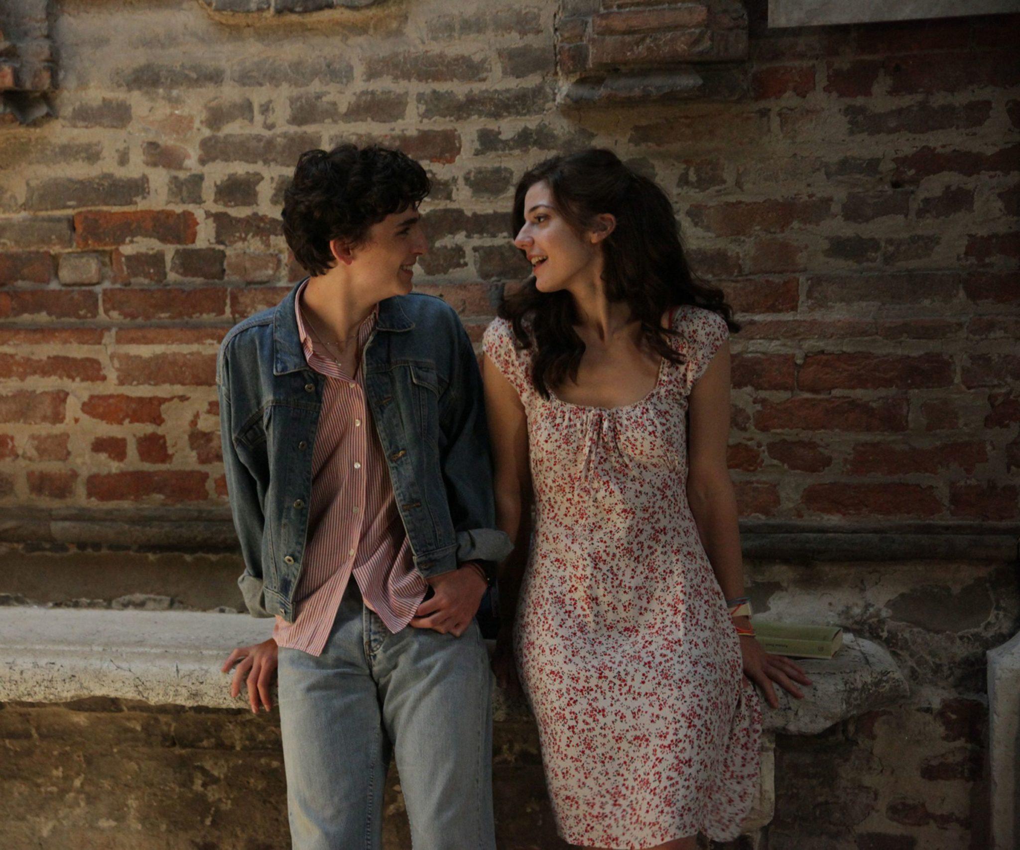 Nastoletni chłopiec i dziewczyna uśmiechają się do siebie, opierając się o mur.