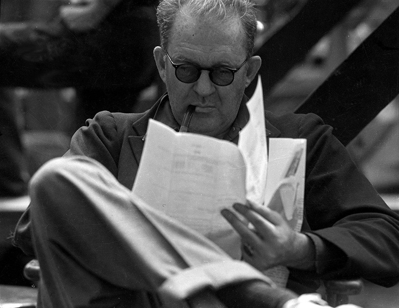 Reżyser John Ford siedzący z fajką i czytający scenariusz