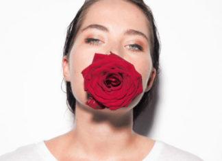 Na bialym tle portret kobiety brunetki ubranej w biala koszulke z czerwona roza w ustach