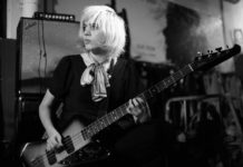 Na czarnobialym zdjeciu widzimy krotko scieta blondynke ubrana w ciemna sukienke pochylona z gitara elektryczna na tle glosnikow