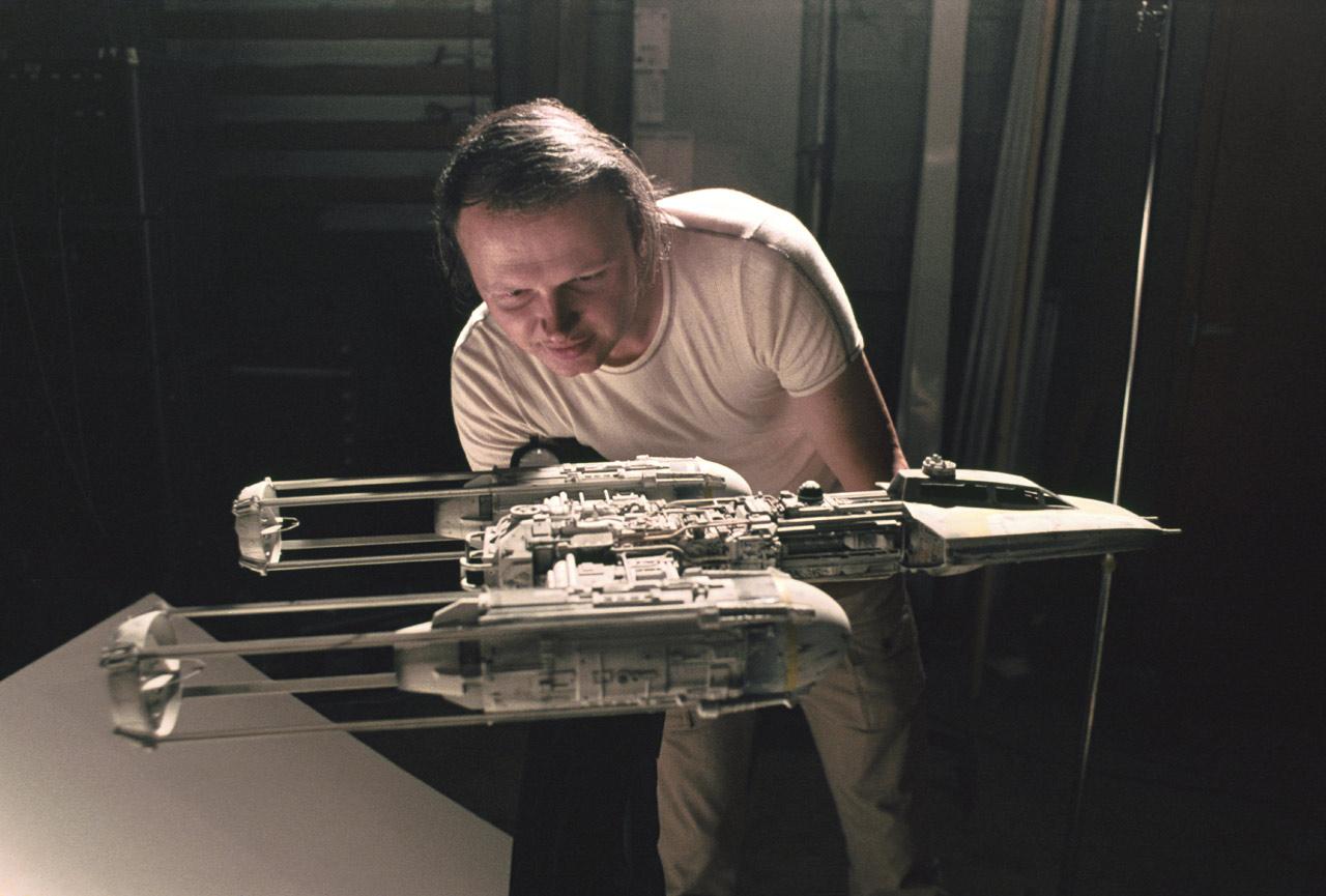 Dennis Muren pochylający się nad makietą statku kosmicznego z Gwiezdnych Wojen
