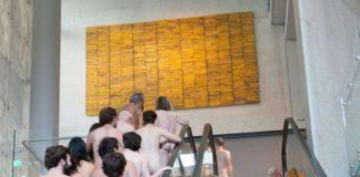 Grupa nagich osób jadąca w górę schodami ruchowymi, naprzeciwko nich żółty obraz - dzieło sztuki współczesnej.