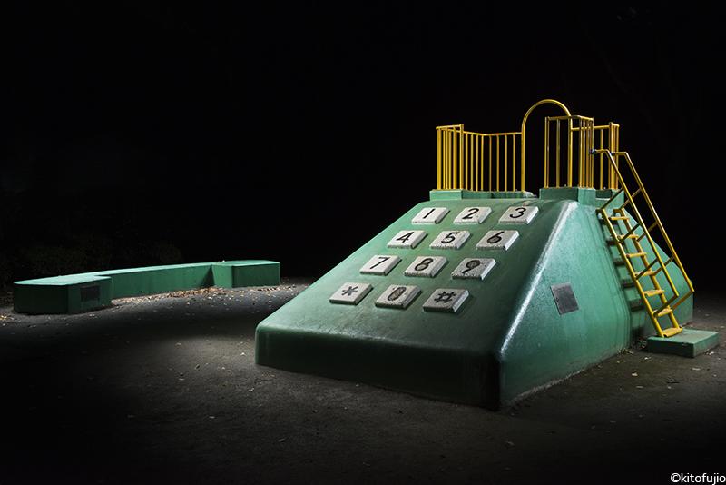 Duży, betonowy element placu zabaw w formie zielonego, starego telefonu stacjonanego i słuchawki.