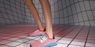 Nogi ubrane w buty adidasa z kratką na kraciastej podłodze