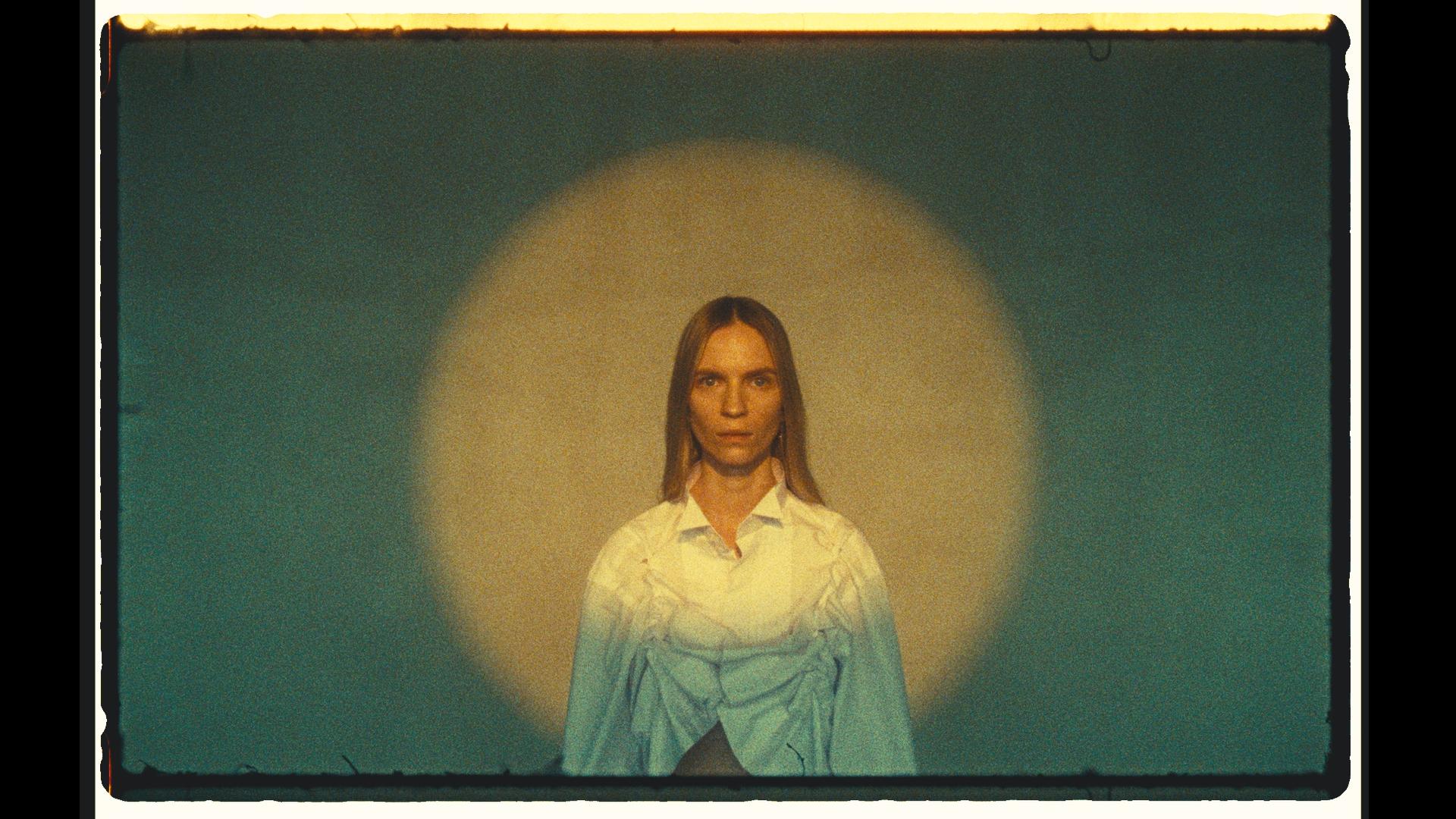 Na zdjeciu widzimy kobiete w blond dlugich wlosach na tle swietlistej kuli w bialej koszuli
