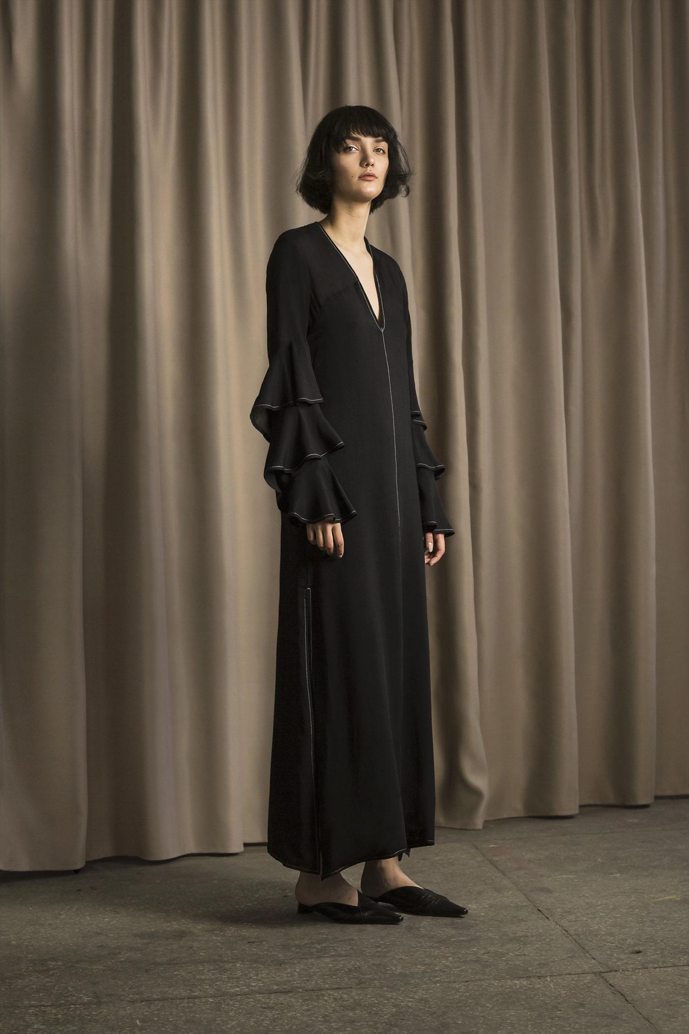 Na zdjeciu widzimy kobiete w krotkich wlosach ubrana na czarno w midi spodnice i bluzke na brazowym tle zrobionym z materialu