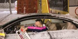 Mężczyzna w zaśnieżonym samochodzie z samplerem w ręku