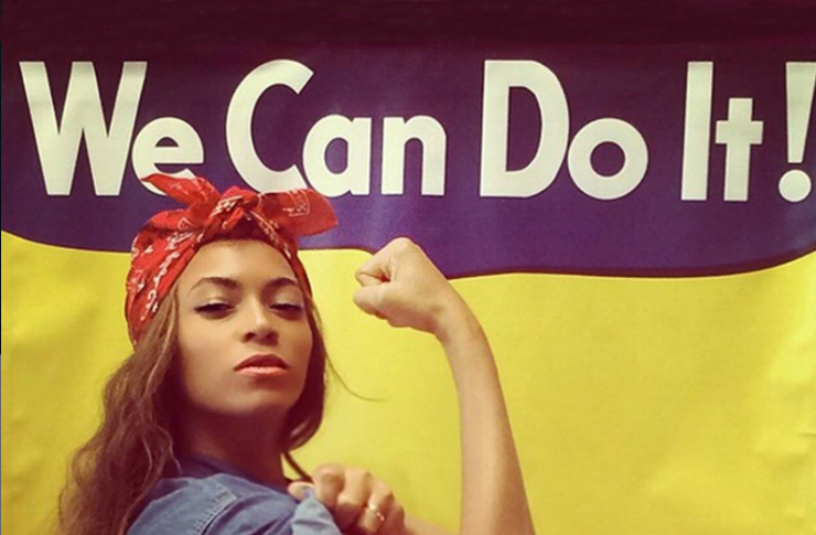 """Ciemoskóra kobieta z czerwoną chustką na głowie w dżinsowej koszuli pokazująca gest siły, żółte tło z napisem """"We Can Do It""""."""