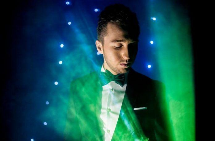 Mężczyzna w smokingu na tle różnokolorowych świateł