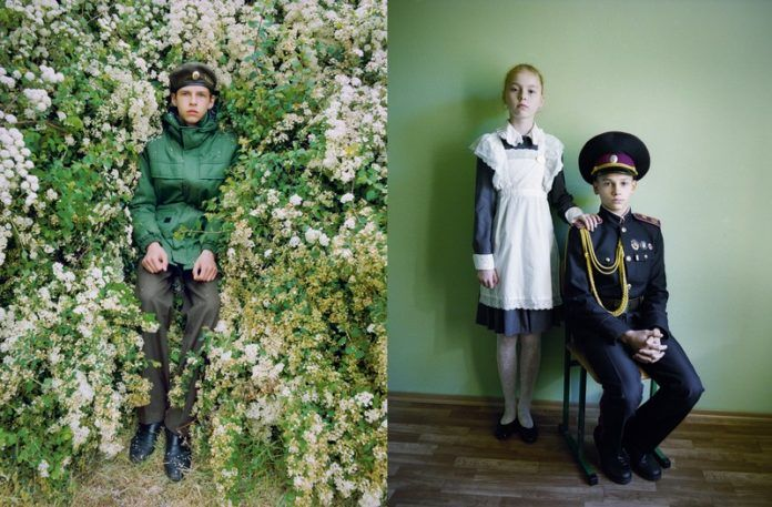 Chłopak leżący w liściach i dziewczynka z chłopcem ubrani w tradycyjne płciowo stroje - pokojówki i żołnierza