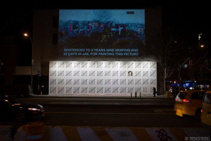 Ulica po zmroku, na ścianie wielki mural, na białym tle seria czarnych kresek przypominających kraty więzienne, za jedną wizerunek kobiety, w prawym dolnym rogu napis