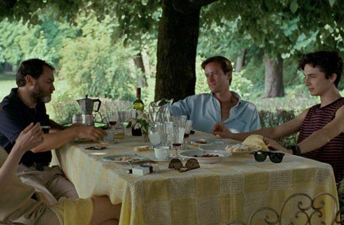 Ogród w którym jest stół przy którym siediz grupa ludzi