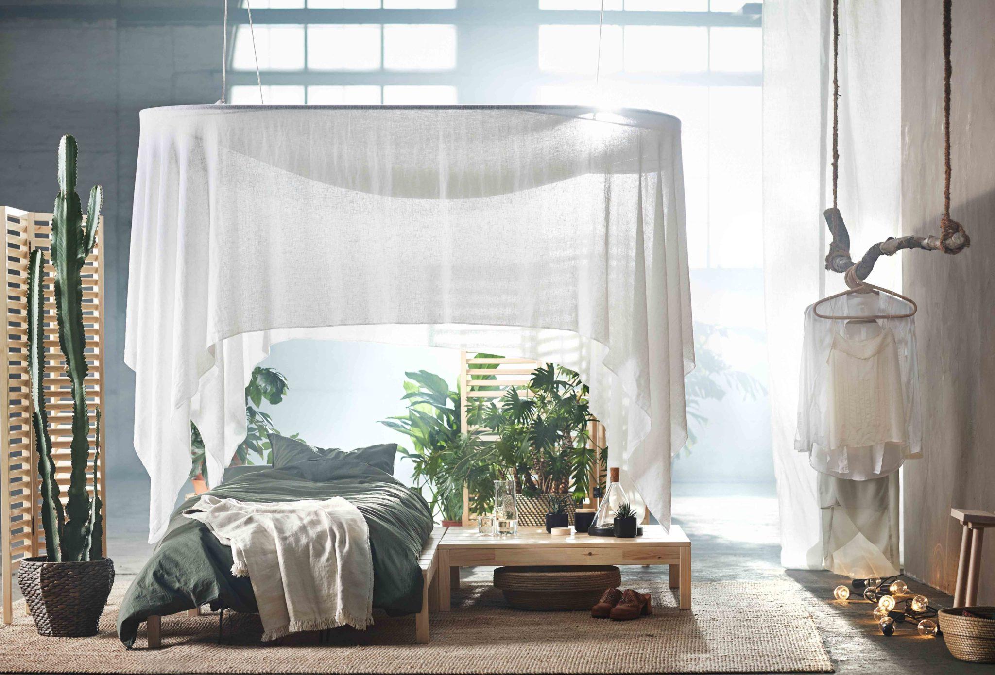 Jasne, oświetlone światłem naturalnym pomieszczenie z łóżkiem pojedynczym i drewnianym stolikiem z roślinami i szklanymi naczyniami pod białym baldachimem.