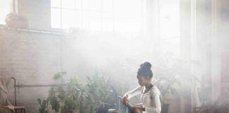 Ciemnoskóra kobieta ubrana w białą koszulkę i szare spodnie dresowe zwija niebieską matę do jogi, jest w dużym, oświetlonym pomieszczeniu, wypełnionym roślinami i świecami.